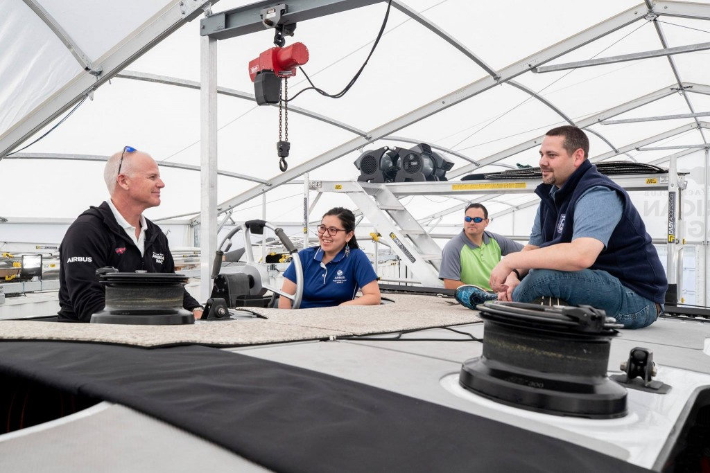 L to R: Terry Hutchinson shows Seng-Ai Liaw, Joshua Powell and Josh Cochran some of the steering techniques of the flying boat.