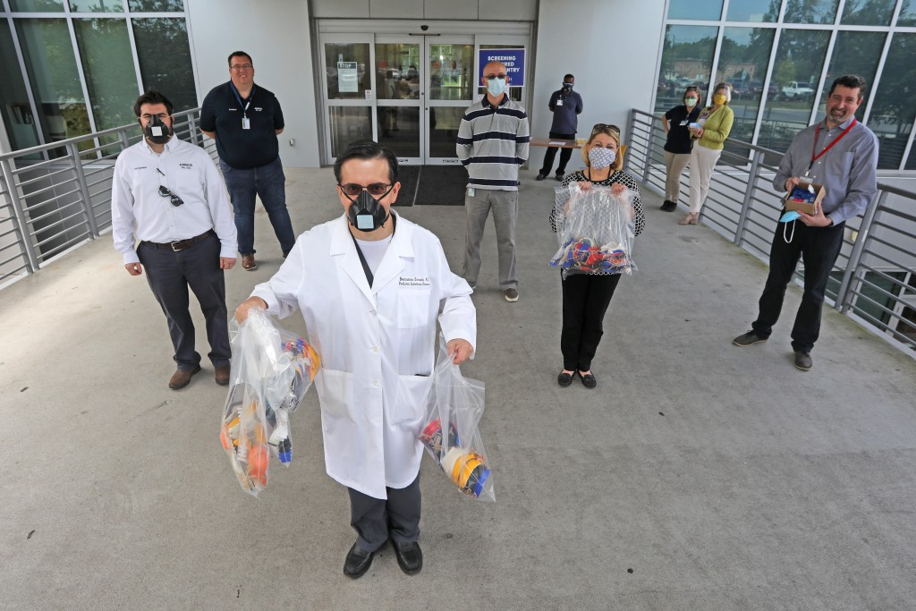 Dr. Benjamin Estrada, pediatric infectious disease specialist with USA Health, assistant dean for educational strategies and faculty development; professor and vice chair of Pediatrics at the USA College of Medicine, holds bags of 3D printed masks as he poses for a photo with representatives of Airbus Friday, April 17, 2020.